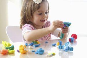 niña jugando con juguetes de piezas